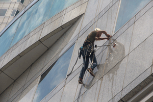 man-cleaning-windows-on-rope-re-size